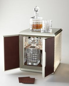 """Waterford London Desktop Bar - is the perfect mix of centuries-old craftsmanship and modern design. It lights up when opened. The illuminated potable bar is made of crystal and leather. It includes four leather coasters, 13""""Sq. leather tray, 26-ounce square crystal decanter, 32-ounce round crystal decanter, two crystal double old-fashioned glasses, and two crystal highball glasses."""