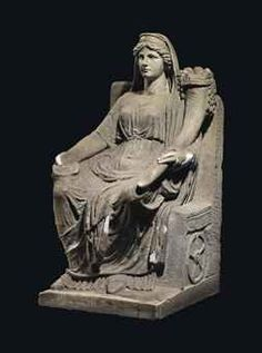 A ROMAN MARBLE FORTUNA CIRCA 1ST-2ND CENTURY A.D. Depicted seated on a high back throne with tasselled cushion, holding a laden cornucopia in the crook of her left arm, a patera in her right hand, wearing a belted chiton with buttons along the right sleeve which is falling off her right shoulder, a himation draped around her waist and lower body, wearing a veil and crescent diadem, the throne decorated with rudder and ball on the right side and wheel on the left side