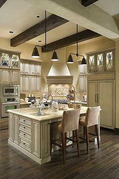 Pretty wood floors with antique white painted kitchen cabinets. Love the X mullion glass doors and the hood in the corner. Great design is done by great kitchen designers...www.soflohomedesign.com Serving Palm Beach County
