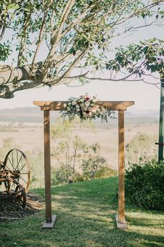 Simple rustic country outdoor wedding ceremony with wooden arbour and flowers | Sophie Baker Photography