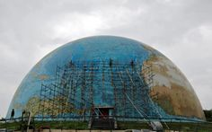 Workers remove scaffolding from a replica of planet earth after repairs at Science City in Ahmedabad, India.