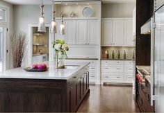 """White and stained wood cabinetry. Gorgeous """"mercury"""" like galss pendants over island"""