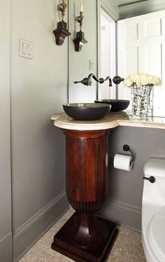 A vintage wood pedestal supports a bowl sink in the powder room. - Traditional Home ®/ Photo: Werner Straube / Design: Julio Quiñones