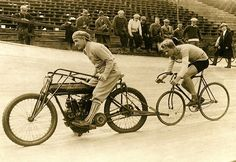 Circa 1910 -- A track cyclist is shown in practice behind an early Indian motorcycle