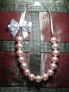Collar de.perlas en tono rosa con cinta y moño color plata