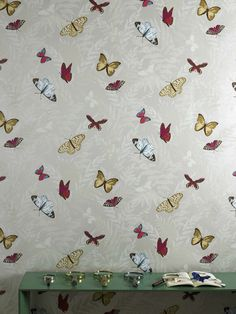 Farfalla wallpaper, one of Nina's absolutely best sellers. Colourful butterflies dancing across a slightly metallic background.