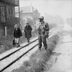 Once Upon a Time in War: French civilians passing a British MP of No. 6 Beach Group in La Brèche d'Hermanville/6 June 1944.