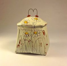 Fun earthenware jar with whimsical daisies.