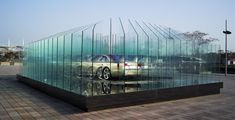 atelier FCJZ: AUDI haus- glass panels are arranged to produce multiple reflections of the car,  eventually blending into each other, creating the illusion of movement and rotation as the viewer walks around the display.