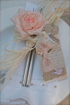 i like the idea of wrapping the silverware in a rose with straw or twine- Elena- I wonder if we can speak to food and bev and ask to do this? maybe put a different pretty flower in place, and sans the weird tag in this photo