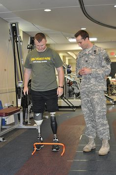 Capt. Bradley Ritland, chief, amputee section physicial therapy, Walter Reed National Military Medical Center, watches Marine Cpl. Garrett J. Carnes practice stepping over small hurdles, 2:23 p.m., July 27. The hurdles help patients with mobility challenges and prostetic lower limbs learn how to negotiate stairs and curbs while maintaining balance. (Photo by Gail Cureton, NRMC HQ PAO)