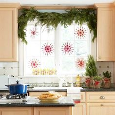 Fabulous way to add festive cheer to a kitchen. An evergreen garland valance, burlap wrapped mini trees & hanging snowflakes for a punch of color. So pretty!