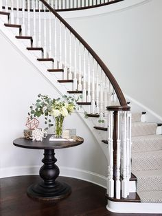 Curved Staircase with painted white risers. Geometric carpet runner and stained treads. Round pedestal table in foyer. Interior design by SHOPHOUSE Interior Designers