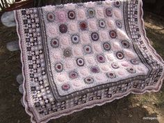 Crocheted afghan with poufy central granny circles and very small granny squares as a border (no pattern)