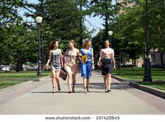 Four beautiful fashion women walking on the street in Moscow city