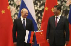 Russian and Chinese national flags are seen on the table with Russian President Vladimir Putin and his Chinese counterpart Xi Jinping stand in the background during a signing ceremony at the Diaoyutai State Guesthouse in Beijing, November 9, 2014. REUTERS/How Hwee Yong/Pool