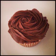 Cupcake de vainilla con frosting de chocolate en forma de rosa