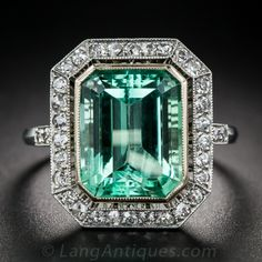 5.50 Carat Green Beryl and Diamond Ring - A bright and clear mint-green beryl (a light, crystalline version of an Emerald, and this one would be called one by most people), weighing 5.50 carats, glistens from within a raised bezel inside a frame of bright white single-cut diamonds in this gorgeous cocktail ring, hand fabricated in platinum during the early-20th century. The under-gallery is expertly hand pierced and the diamond-set shoulders have a delicate scroll support adding that special…