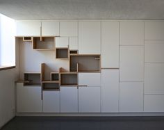 Storage wall cabinets with no handles. Spaces between cabinets are ignored in fabor of the wood design to the left. That are could be kitchen space.