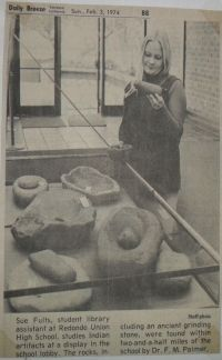 "[ Transcribed (caption) ]  ""Sue Felts, student library assistant at Redondo Union High School, studies Indian artifacts at a display in the school lobby. The rocks, including an ancient grinding stone, were found within two-and-a-half miles of the school by Dr. F. M. Palmer."""