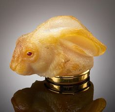 Carved Agate Box in the form of a Rabbit's Head By Manfred Wild Idar-Oberstein, Germany  Carved from a single large piece of fine-quality translucent, yet variegated natural brown agate, with inset ruby cabochon eyes, the base and piano-hinged lid rimmed in a substantial amount of 18K yellow gold. Length 3 1/2in