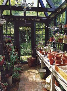 Inside the greenhouse, dry-laid brick floors allow excess water to soak into the ground, while a long counter affords plenty of space for starting seeds and potting up containers. Window shelves are lined with plants, while potting soil and supplies are stashed under the counter.