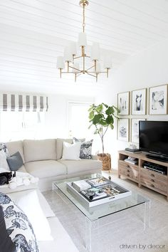 Family room with slipcovered sectional, two-tiered chandelier, acrylic coffee table, and reclaimed wood media console - sources included in post!