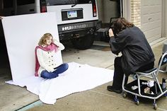 White or black Sheets or blankets mount the back one on foam core, card board or scrap wood + natural light at edge of garge = instant glamour shots / photo studio