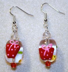 """Handcrafted by Teal Palmetto, LLC. Christmas/holiday gifts for both of your ears!  The glass """"gift"""" focal beads are clear and are handpainted in red, yellow, pink, and green. Each earring has a clear """"crackle glass"""" accent bead at the top, and a red seed accent bead on the bottom.  This pair has silver fish hook ear wires. Price: $14."""