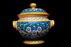 A tureen is a serving dish for foods such as soups or stews, often shaped as a broad, deep, oval vessel with fixed handles and a low domed cover with a knob or handle. This piece of art presents a ceramic lid, which keeps the food hot. The decor features flowers tied by volutes, berries and polychrome bands, make the product particularly elegant.