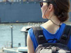 Junge Frau in blauem Shirt mit Rucksack und Sonnenbrille im Sonnenschein am Hafen der Hansestadt Hamburg an den St. Pauli Landungsbrücken