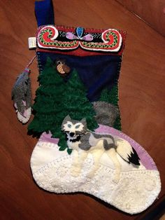 Beautiful, unique, and handmade Christmas stocking. On a background of midnight sky, the lone wolf pads softly through the evergreen forest under the