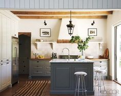 The kitchen cabinets and custom-made island are painted inBenjamin Moore'sWhite Dove and Arctic Shadows, respectively, and the backsplash is made of ceramic tiles byExquisite Surfaces; the refrigerator is byViking, and the barstools are fromDesign Within Reach.