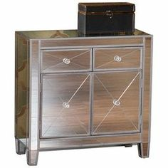 "2-drawer mirrored cabinet with a center compartment and faux crystal knobs.       Product: Cabinet  Construction Material: Wood and mirrored glass  Color: Silver   Features:   Two drawers  One large double door storage cabinet  Faux crystal knobs  Dimensions: 28"" H x 28"" W x 13"" D   Assembly: Assembly required"