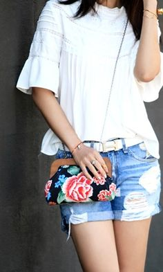 Floral printed clutch with a wooden frame and chain link shoulder strap