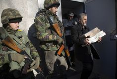 Ukrainian army soldiers guard a district election commission as an election official carries ballots to a polling station in Volnovakha, a village on the front line of fighting between Ukrainian government forces and rebels, eastern Ukraine Saturday, Oct. 25, 2014. (AP Photo/Dmitry Lovetsky)