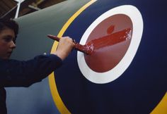 A young woman worker painting the fuselage roundel on a Mosquito aircraft at de Havilland's factory at Hatfield in Hertfordshire, 1943.  Ministry of Information official photographer  © IWM (TR 918)