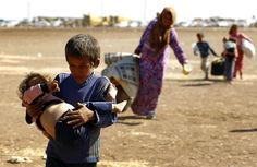 A young Syrian Kurdish refugee boy carries an infant after crossing the Syrian-Turkish border, near the southeastern town of Suruc in Sanliurfa province September 23, 2014. More than 130,000 Syrian Kurds fleeing an advance by Islamic State militants have crossed into Turkey in the past three days and the authorities are preparing for more, Turkish Deputy Prime Minister Numan Kurtulmus said on Monday.