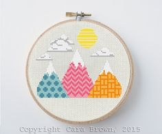 Instant download pattern for a counted cross stitch of a colorful mountain range with sun and clouds. This modern needlepoint project makes a nice