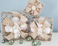 """Beach Christmas decor jute seashell decorative gifts. These gorgeous coastal Christmas decor shell enhanced burlap presents come in 3 sizes and are created not to match, but to """"go"""" with each other in perfect coordination. These gorgeous nautical Christmas decor decorative gifts are built on a metal cage for strong support, then covered in jute roping and ribbon, topped with a generous sprinkle of sparkly glitter and a bit of white """"snow"""".  10"""", 8"""" and 6"""" square dimensions."""