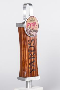 """Tap Handle No. 19123""—S. Casey Gleason. Tap Handle No. 19123 is crafted out of scrap wood and aluminum. The wood body is shaped, carved, and burnt for the grip of a brawler, while an extra special hand may love to pull from the brushed aluminum loop. This tap handle design gives a nod to Philadelphia's industrial history and celebrates our modern day revolution to bring back a handcrafted sensibility to the forefront of our culture."