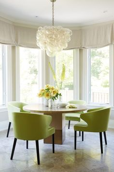 In the airy breakfast nook, a whimsical Oly Studio pendant light hangs above a Van Rossum dining table. Hepfer chose apple-green chairs to help brighten the space and bring the outdoors in.
