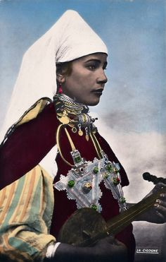 *|*  Morocco, woman from Tinzit (Southern Morocco).  beginning of 20th century.  You can also see a black and white version of this image here http://commons.wikimedia.org/wiki/File:Musicienne_aux_bijoux.jpg
