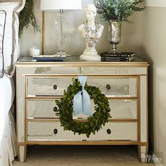 Simple accessories in the bedroom bring the holiday spirit to life. A petite wreath hangs from a mirrored nightstand and repeats the natural appeal of the lush swag above the headboard. Glittering garland and sprigs of fresh greenery fill a mercury-glass-style urn. /