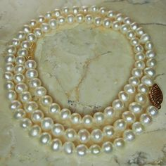 A classic pearl necklace in ivory color with a 14K yellow gold clasp. Each pearl measures approximately 5mm in diameter. The strand is 18 long including clasp when unclasped and layed out flat. The pearls are not perfectly round but are nicely matched in color and size and in excellent condition. The pearls are strung on a strand, these do not have knots between each pearl. The clasp is a hook and lock style decorative filigree clasp that is stamped 14K FIC. The pearls hang tightly with no…