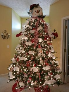 Red and white christmas tree with large snowman head as a topper. Fun decor