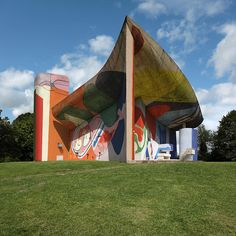 colored organic shapes and motifs have been digitally overlaid onto the chapel's unique architectural facets, wrapping around its crab shell roof, concrete façades, and the small, irregular windows it has become best known for.