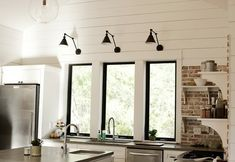 White wood paneled walls, open shelving, beautiful windows, great light fixtures, stainless steel, & exposed brick. Yes, please!