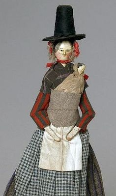 A rare wooden doll in traditional Welsh costume holding a baby in the Welsh fashion Circa 1850.