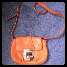 Michael Kors Crossbody This orange Michael Kors crossbody bag is perfect for any MK lover! NWOT- never used. See image 4 for slight scuffing on the front buckle (purchased as such).  Features two interior pockets and one exterior pocket. 100% authentic. No dustbag. No trades, Posh rules only! Michael Kors Bags Crossbody Bags